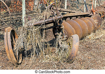 Vintage Rusted Discarded Agricultural Plough Covered with Grass
