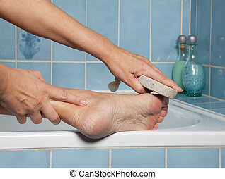 Callous feet and pumice stone - Hand removing callus from...