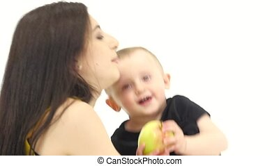 Girl kisses her baby, he laughs. White background. Slow...