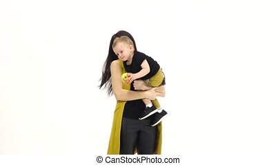 Mother kisses her baby, he laughs. White background. Slow motion