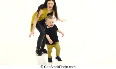 Child runs on the floor in a spacious room. White...