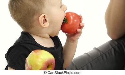 Baby is eating a tomato, and is crooked. White background....