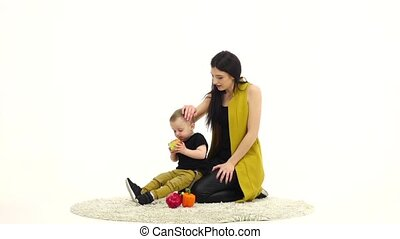 Baby eats an apple, next to her mother. White background....