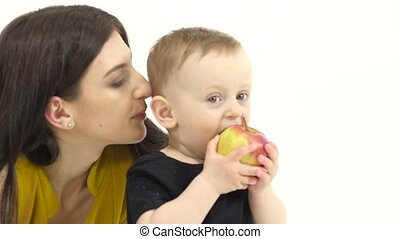 Baby eats an apple, he likes it. White background. Slow...