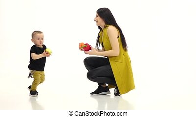 Mom holds two peppers, the baby has an apple and he runs...