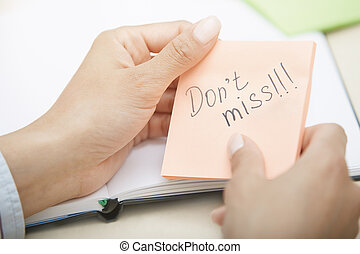 Do not miss - Hands holding sticky note with Do not miss...