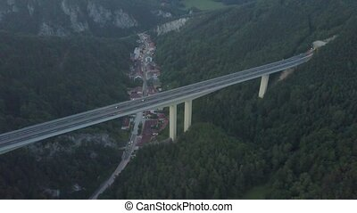 Aerial view of European highway bridge above small town in the evening