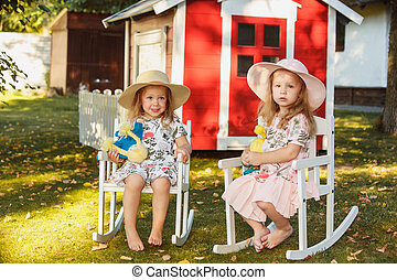 Cute little blond girls in hats sitting on the field with...