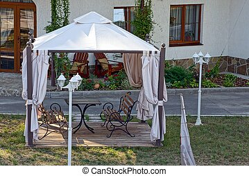 Open gazebo with benches on the lawn with lanterns near the road
