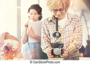 Positive delighted blonde boy looking into eyepiece