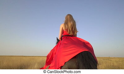 Girl horseback rider wearing long red dress riding horse on country road