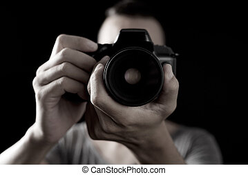 young man with a reflex camera - closeup of a young...