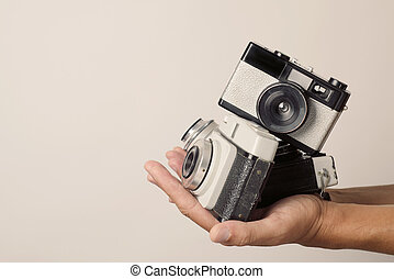 young man with old film cameras - closeup of a young man...