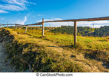 wooden fence along the path through countryside. grassy...