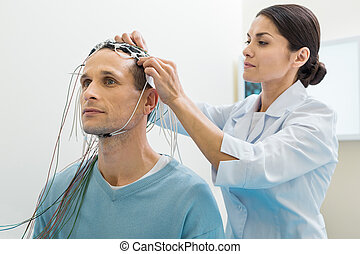 Female doctor putting electrodes on patients head -...