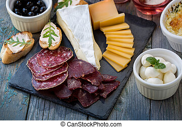 Sliced meat and cheese on the board - Board with basturma,...