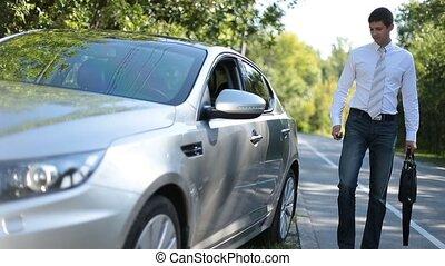 Stylish business executive getting into luxury car - Stylish...