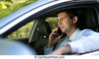 Busy businessman communicating on phone in car - Busy young...
