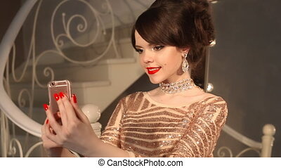 Selfie. Young teenage girl taking photo in golden dress and...