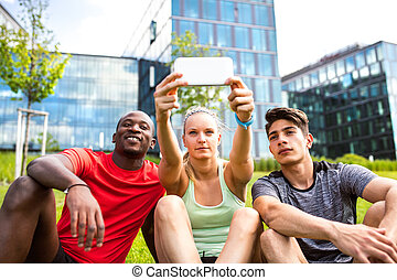 Young runners in the city taking selfie witn smart phone. -...