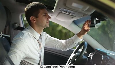 Successful businessman fixing tie in car