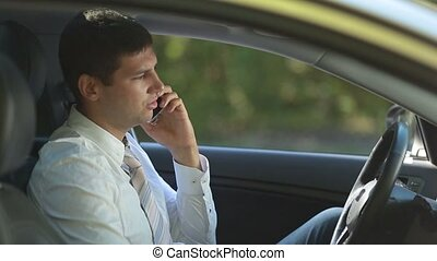 Busy business executive talking on phone in car - Confident...