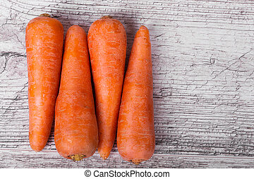 Orange peeled carrot, refreshing vegetables for tasty dishes, smoothies, cakes on a light wooden background. Harvest of carrots.