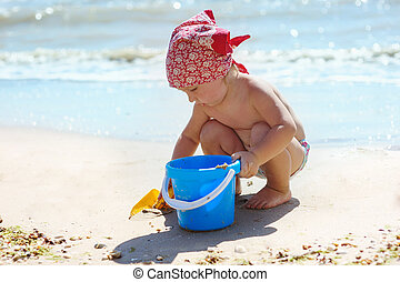 Little girl is playing with a blue bucket by the sea.