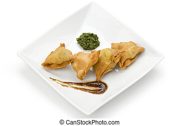 Samosas with green and brown chutney on white square plate.