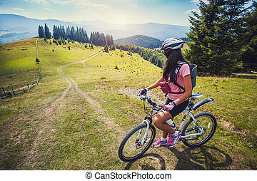 young woman riding a bicycle on the high plateau - Happy...