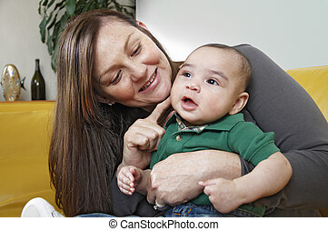 Mixed race infanted smiles while seated on his mothers lap -...