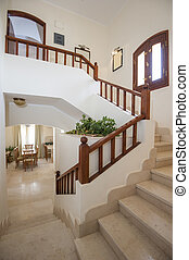 Marble staircase in luxury villa home with wooden bannister...