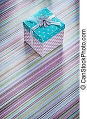 Present box on striped fabric surface directly above...