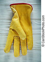 Leather protective glove on wooden board.