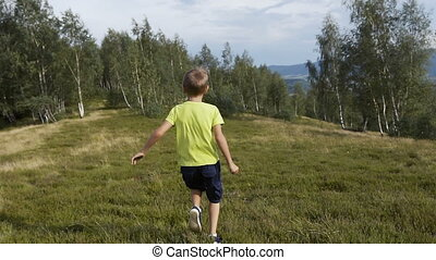 A boy gymnast runs and makes a somersault in the mountains