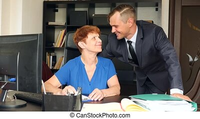 The elderly mother sits in the office at her desk. Her son a...