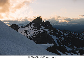 Cloudy moody sunset in snow mountains above Garibaldi Lake on Panorama Ridge