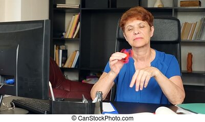 Red hand spinner, or fidgeting spinner, rotating on man's hand. Elderly lady businessman spinning a fidget spinner in his office at his desk. 4k. Slow motion