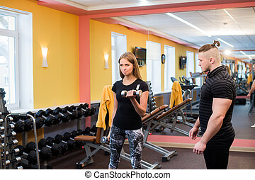 Woman with her personal fitness trainer in the gym...