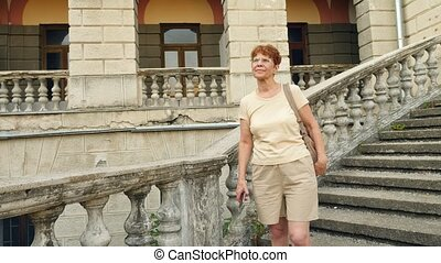 Beautiful elderly woman or tourist taking a photograph with...