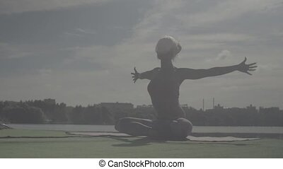 Young woman doing yoga exercises on the river bank -...