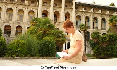 A beautiful elderly woman or a tourist is reading a book in...
