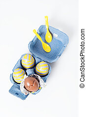 Foil covered chocolate easter eggs with plastic spoons in paper box on white background.
