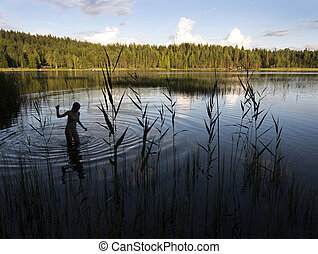sihouette of girl in finnish lake at sunset in summer