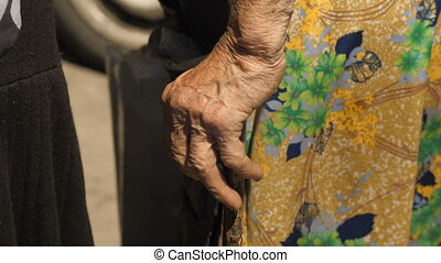 Hand of a old woman with crutch standing on the strret