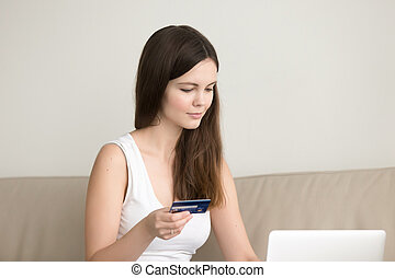 Young lady shopping online at home, paying by credit card -...