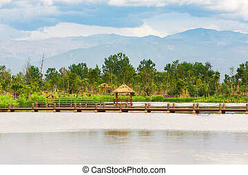Little wood pavilion on a lake with mountains in the background