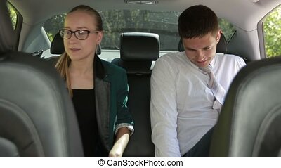 Business colleagues working at the backseat of car -...