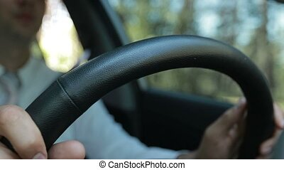 Man hands holding steering wheel while driving car - Closeup...