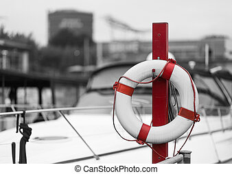 red lifebelt in front of a marina - red lifebelt in front of...